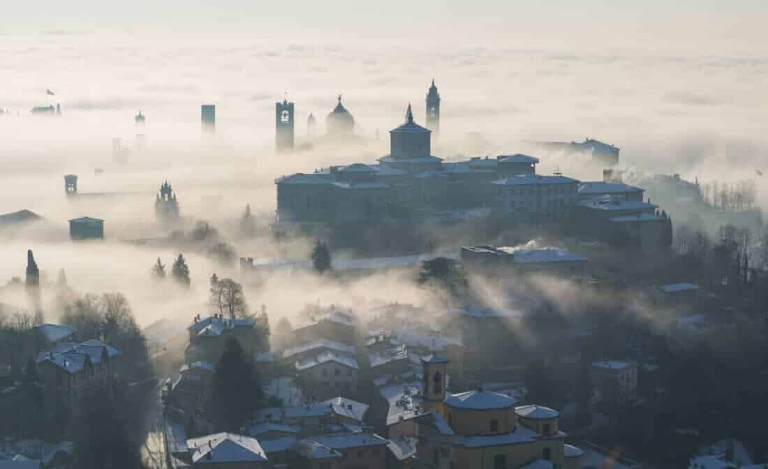 Bergamo, Italy. Lombardy. Amazing landscape of the fog rises from the plains and covers the old town. Architecture, backlight.