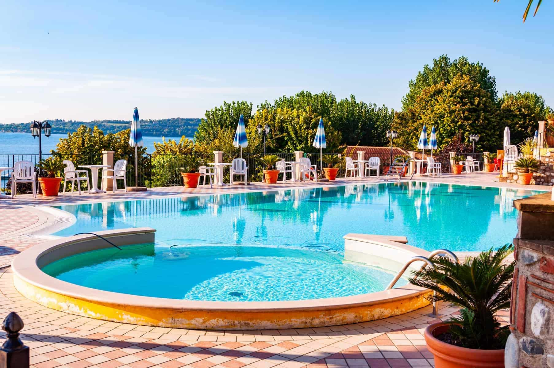 Camping La Ca, Garda Lake, Lombardy, Italy - September 12, 2019: Outdoor pool with vibrant crystal water, parasols and deck chairs located on the coast of Garda lake in amazing La Ca camping in Italy