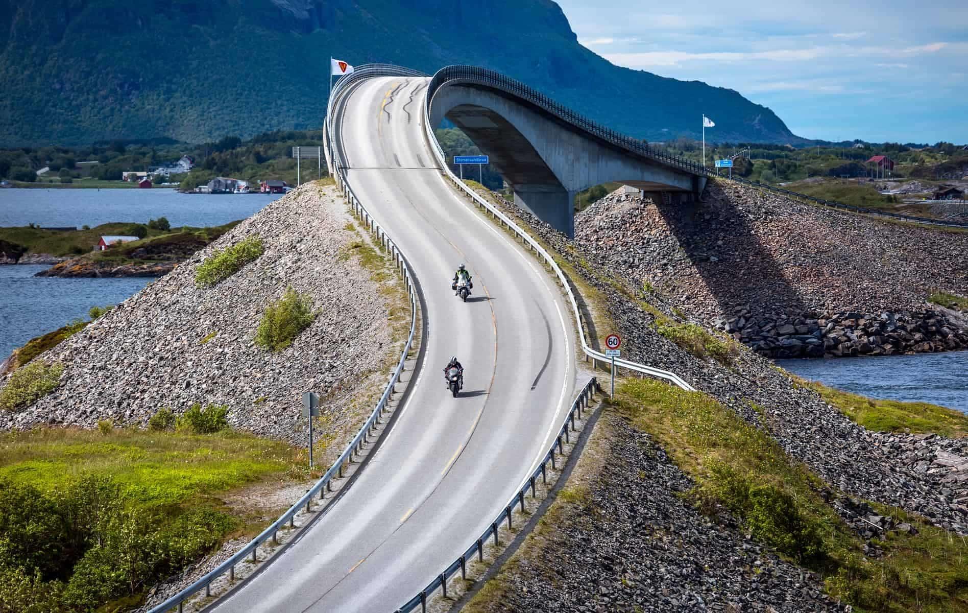 "Two bikers on motorcycles. Atlantic Ocean Road or the Atlantic Road (Atlanterhavsveien) been awarded the title as ""Norwegian Construction of the Century""."