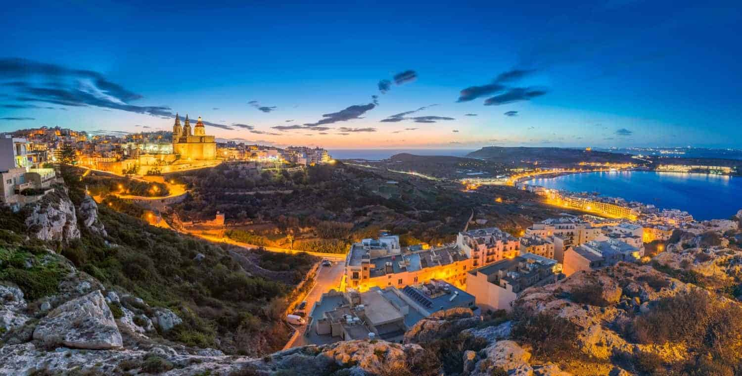 Malta - Beautiful panoramic skyline view of Mellieha town after sunset with Paris Church and Mellieha beach at background with blue sky and clouds