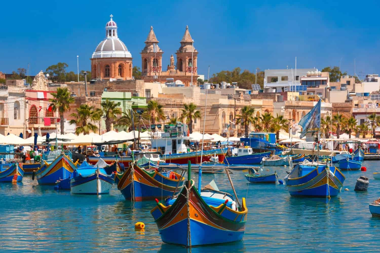 Malta, Traditional eyed colorful boats Luzzu in the Harbor of Mediterranean fishing village Marsaxlokk, Malta