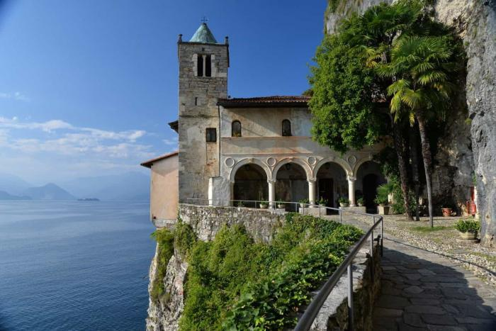 Lago Maggiore. The monastery of Santa Caterina del Sasso built on a cliff flank, hanging above the waters of Lago Maggiore, province of Varese, Italy. Northern Italian lakes.