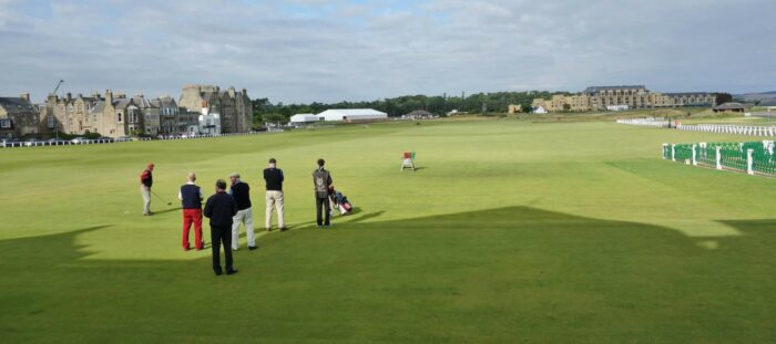 A group of players tee off at historic St. Andrews Golf Course, Scotland.