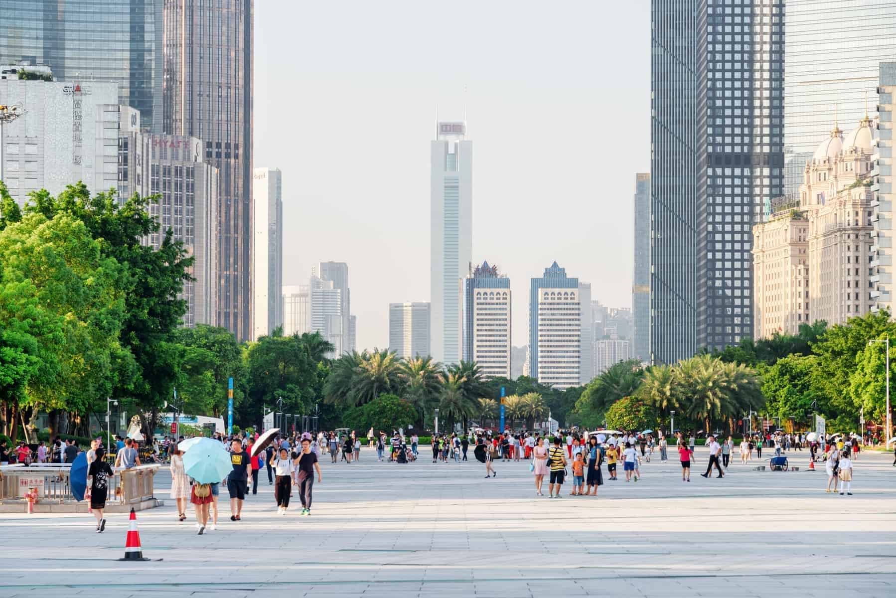 Guangzhou, China : Asian tourists walking in a scenic city park among modern buildings in the Tianhe District of the Zhujiang New Town. Guangzhou is a popular tourist destination