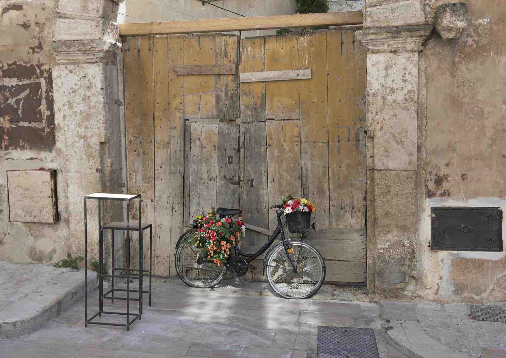 Pictured is a black bicycle with flat tires turned into a display for flowers in front of a closed business in Matera, Italy.