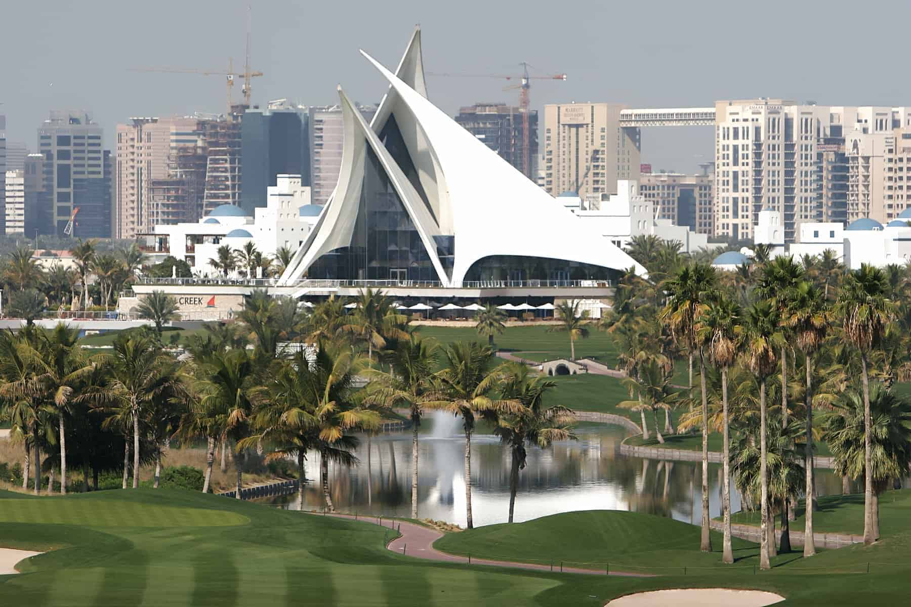 Green golf court with palms and lakes in dubai creek, united arab emirates