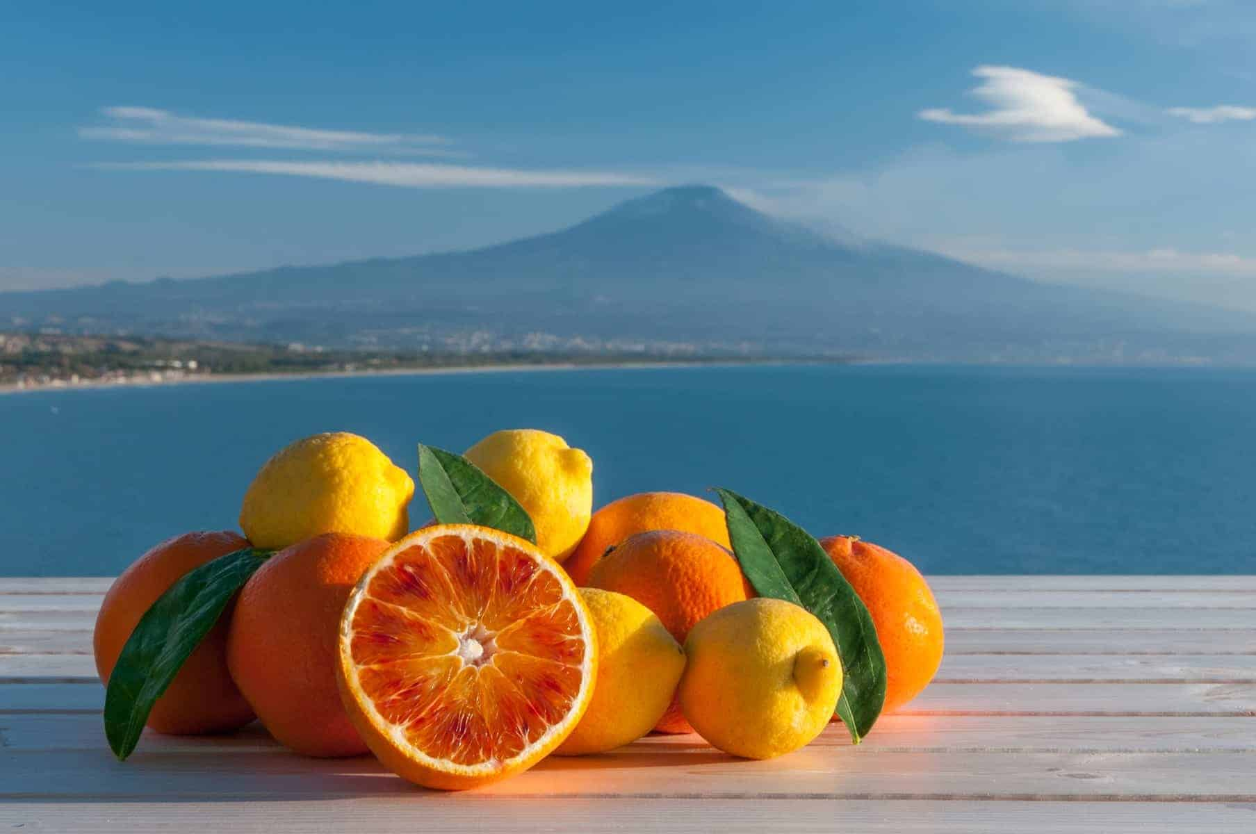 Oranges and lemons on a wooden table with blue sea, Mount Etna and clouds in the background