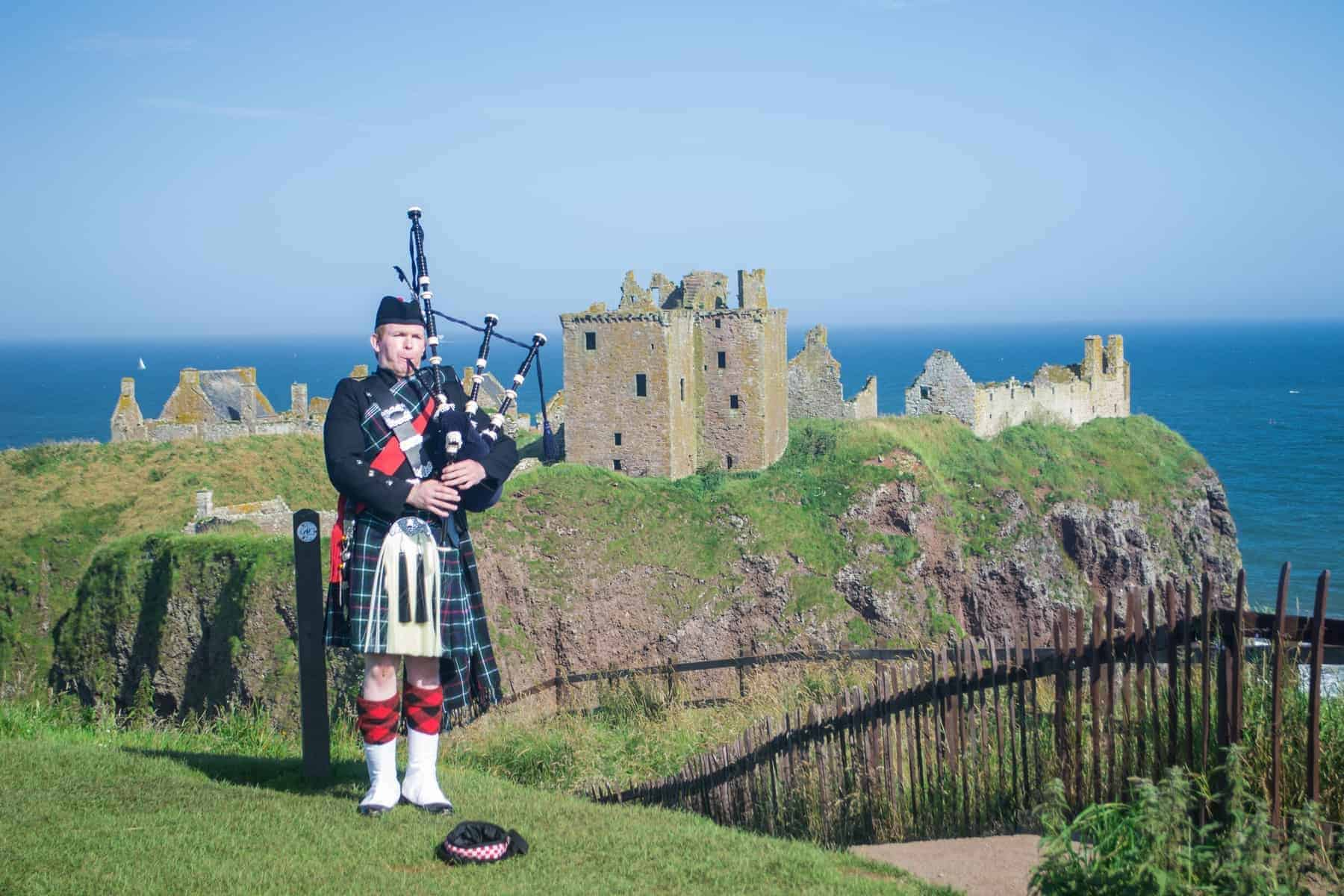 Scottish Piper at Dunnottar Castle, Aberdeenshire, Scotland. He plays pipe with the castle in background