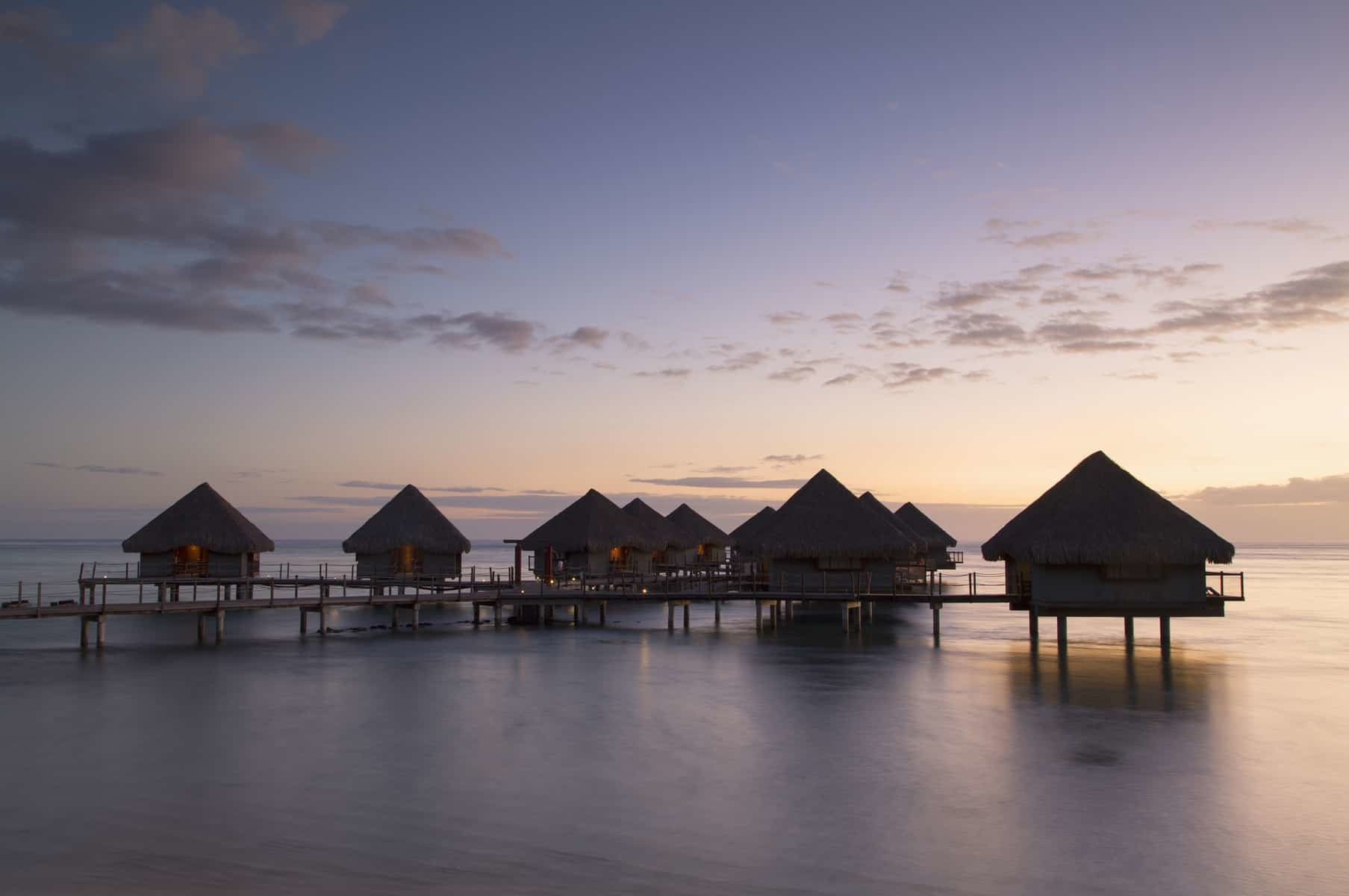Overwater bungalows at Le Meridien Tahiti Hotel at sunset, Pape'ete, Tahiti, French Polynesia