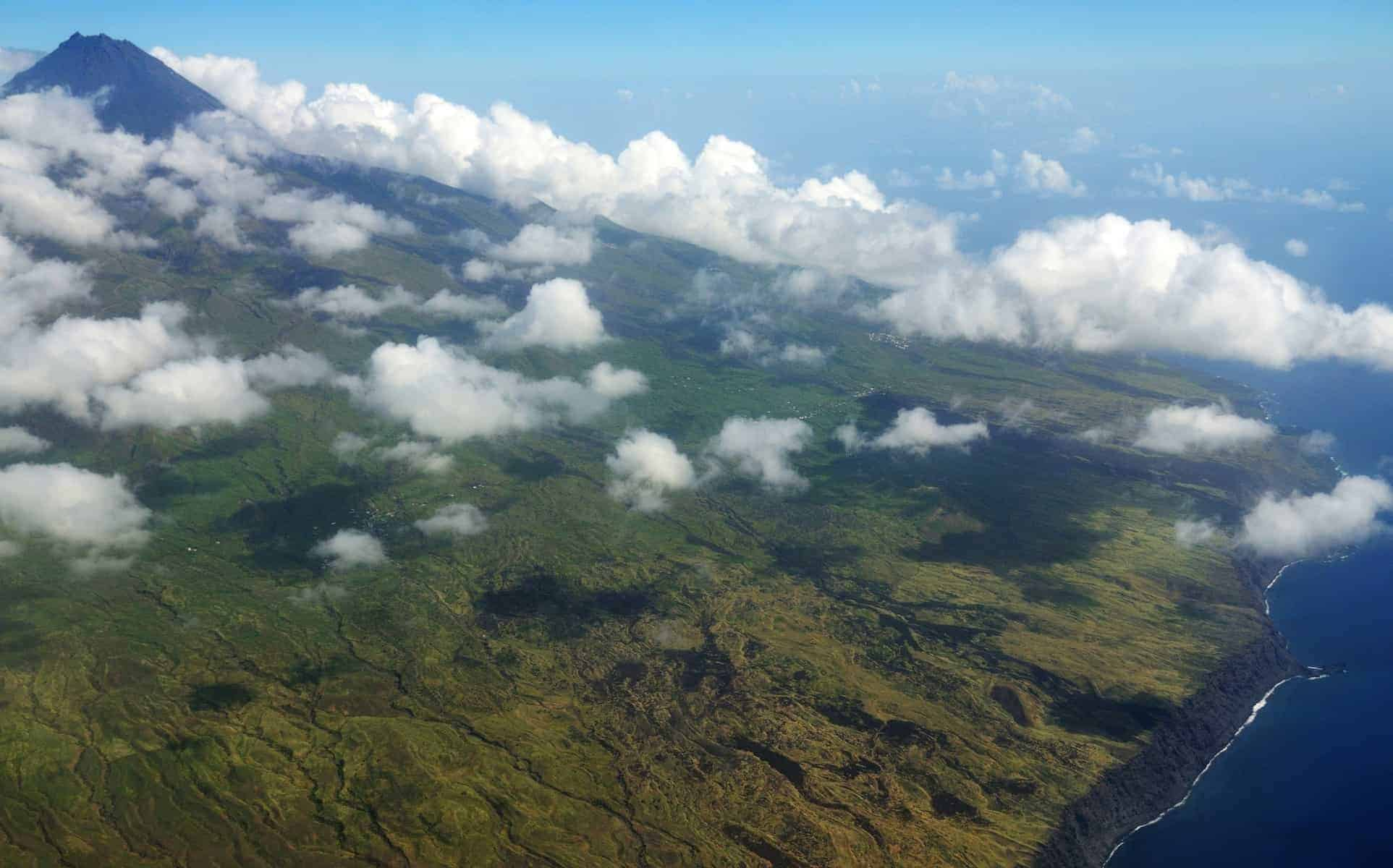 The island of Fogo, in Cabo Verde c0vered by white puffy clouds, as seen from aerial view on departure