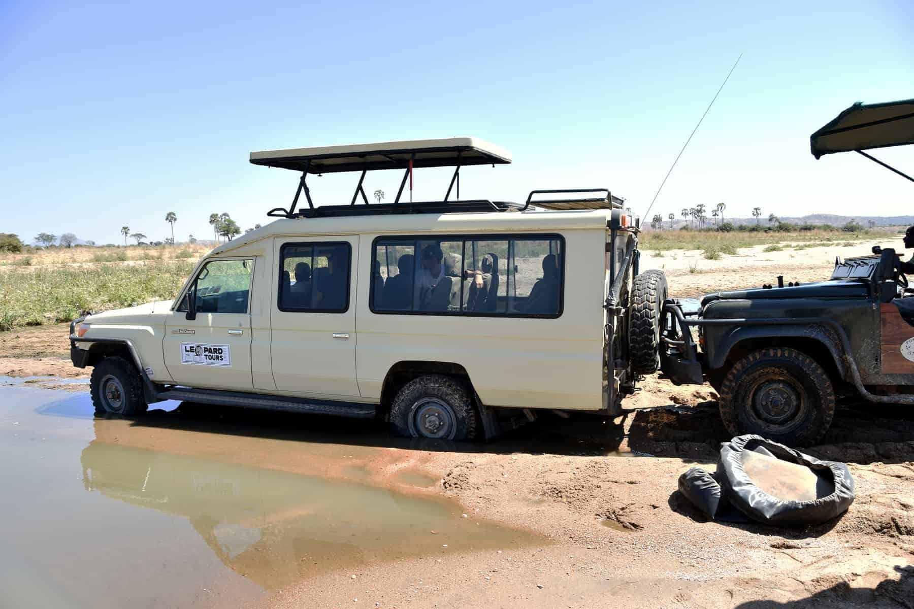 Ruaha National Park, Tanzania, Africa - August 6 2018: a safari car is stuck in the river while another car is trying to push it out, Ruaha National park, Tanzania.