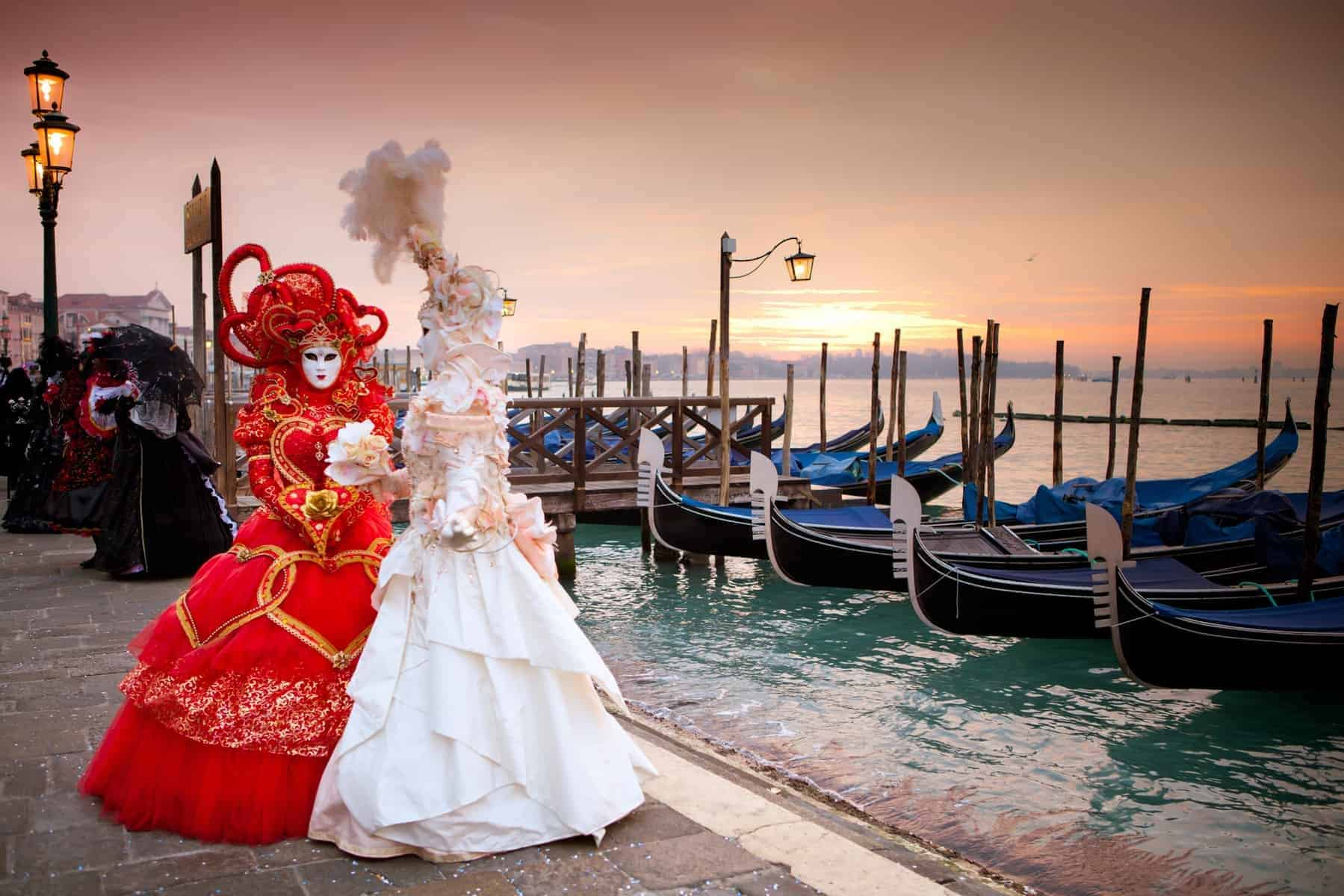 Karneval i Venedig. Sunrise in Venice Italy in front of Gondolas on the Grand Canal Beautiful costumed women