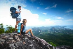 Backpacking: Two hikers with backpacks standing on top of a mountain and looking to a valley