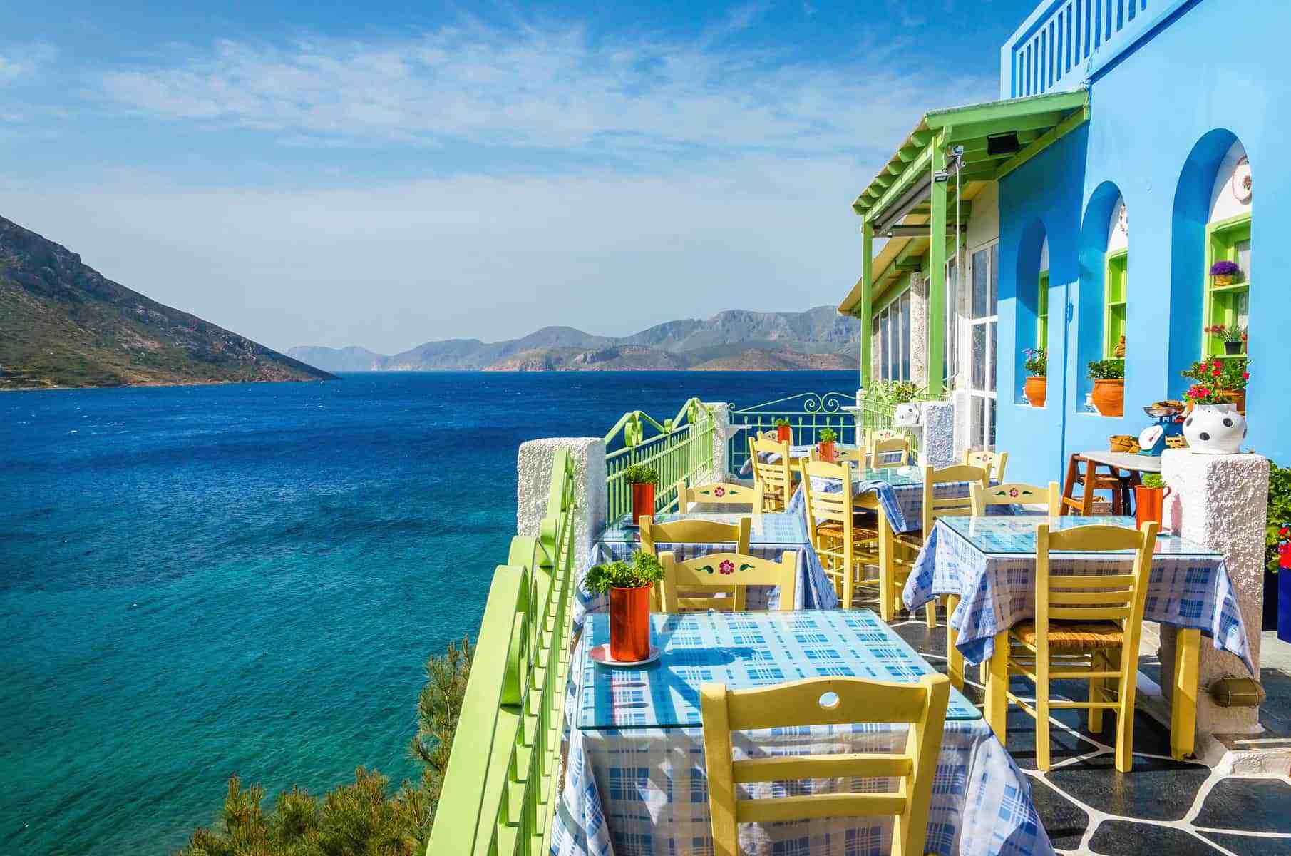 Typical Greek restaurant on the balcony blue building overlooking the sea, Greece