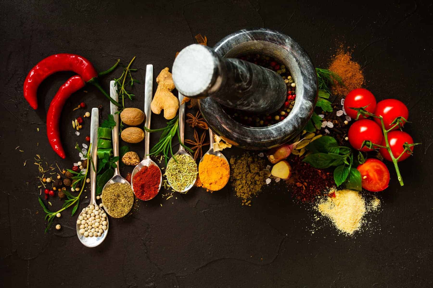 Pepper in a mortar and dry spices on a black background