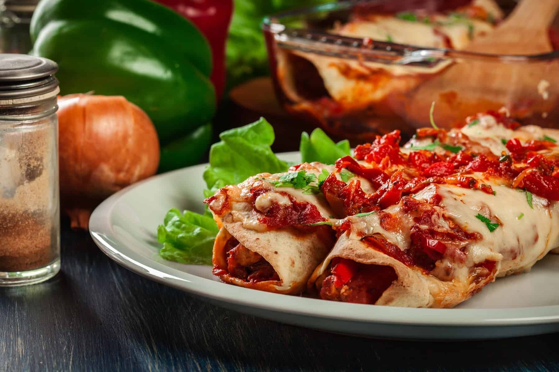 Mexican enchiladas with chicken meat, spicy tomato sauce and cheese on a plate