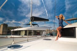 Lords travel. Beautiful young woman in casual wear standing on a yacht fore at Trogir marina, Croatia